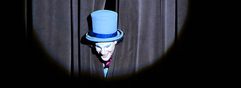 Image of drama performer sticking his head out of the curtain.